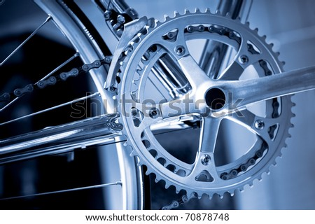 chromed precision racing bike gearwheels and chain with a blue tint