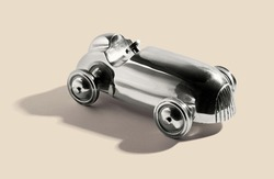 Chromed silver vintage two sealer open sports car toy with integral wheels, on a white beige with shadow