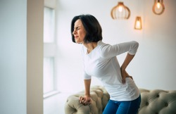 Chronic back pain. Adult woman is holding her lower back, while standing and suffering from unbearable pain.