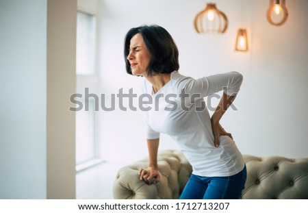 Chronic back pain. Adult woman is holding her lower back, while standing and suffering from unbearable pain. Foto stock ©