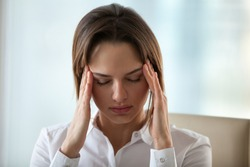 Chronic headache concept, young exhausted woman suffers from migraine touching temples to relieve pain, tired fatigued lady feels dizzy of overwork, stress or hormonal imbalance, headshot, front view