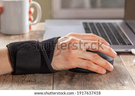 Chronic trauma to the wrist joint  in people using computer mouse may lead to disorders that cause inflammation and pain. A woman working on desk uses wrist support brace and ergonomic vertical mouse Сток-фото ©