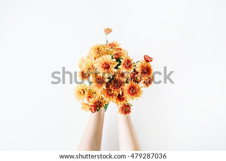 chrysanthemum bouquet in girl's hands on white background. flat lay, top view concept