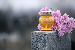 Chrysanthemum flowers and candle on grey granite tombstone outdoors. Funeral ceremony