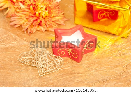 chrysanthemum, gift and red candle on gold background