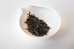 Chuan Cheng (2013) sheng Pu Er tea leaves in a porcelain container . Beautiful top view photography of the dry aged tea leaves from Yunnan province in China.