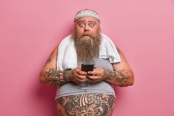 Chubby shocked man with thick beard, stares at camera, busy with sport training, dressed in sportswear cares about his weight uses cellular for checking how much calories were burnt. Sport, motivation