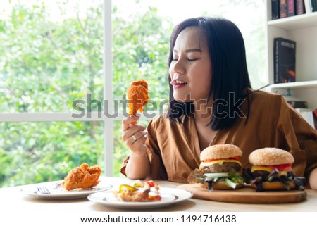 Chuby woman eating a large piece of fried chicken in the living room with a lot of fast food on the table. She stuck her tongue out of hunger and thirst and stared at the object with excitement.