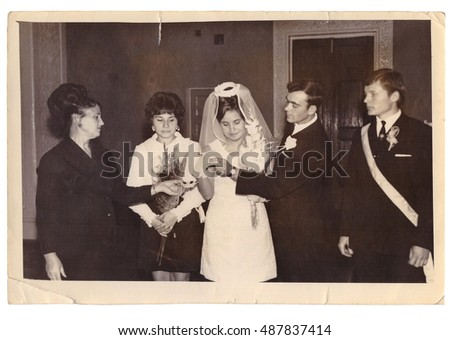 CHUDNOV, UKRAINE - CIRCA 1960: Employee of Civil Acts Registration Office carries out solemn ceremony of marriage of bride and groom in presence of witnesses (vintage photo, approximately 1960s)