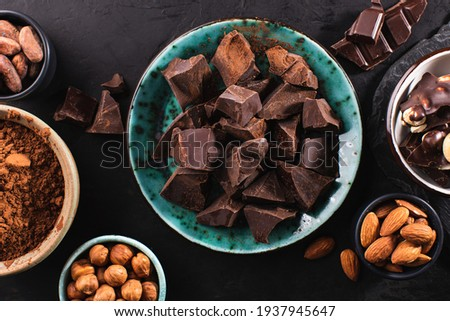 Chunks of dark chocolate on a plate, melted chocolate in a bowl and cocoa beans on a dark textured background. Chocolate confectionery background.