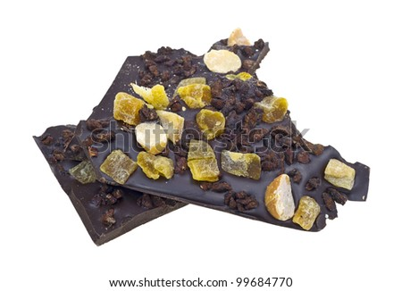 Chunks of dark chocolate with mango chunks and macadamia nuts on a white background.