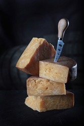 Chunks of hard, perennial cheese on a black background. The cheese is laid in vertical rows. A cheese knife . The concept of still life. Natural dairy product. Vertical photo.