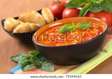 Chunky tomato soup made of tomatoes, carrots and onions and garnished with a basil leaf (Selective Focus, Focus on the basil leaf on the soup)