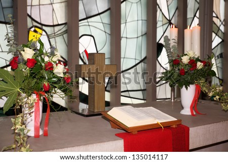 Church altar with cross, flowers and bible