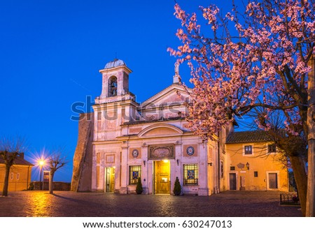 Church and Shrine of the Mother of Divine Love (Madonna del Divino Amore) outside Rome, Italy, at blue hour with spring blossom trees. Stockfoto ©