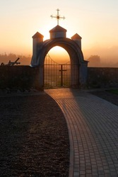 Church architecture. A stone gate with an arch and a Catholic cross above it. Morning. fog