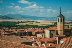 Church bell tower amid rooftops and countryside landscape in Avila. A cute city with medieval buildings in Spain.