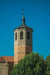 Church bell tower made of bricks and green trees with blue sky, in a sunny day at Avila. A cute city with medieval buildings in Spain.