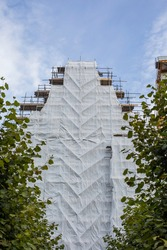 church building facade covered with scaffolding and white cloth for a construction site or construction on the street of a city