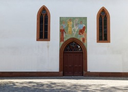 church entrance with wooden door and religious mural, large historical stained glass windows, without people during the day