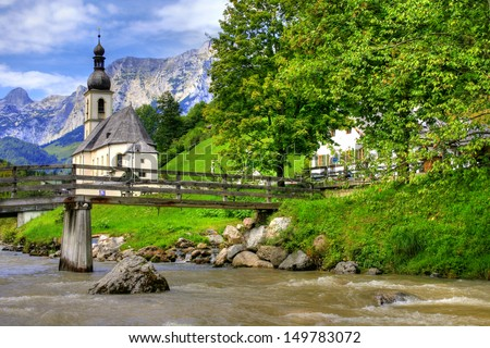 Church in Ramsau (Germany) with mountain brook and wooden bridge