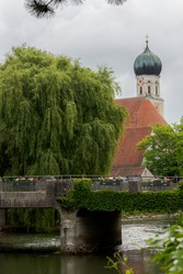 Church of Holy Maria Magdalena and famous old stone bridge over the river Amper in the bavarian town Fuerstenfeldbruck on cloudy overcast day
