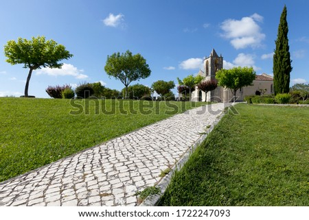 Photo of Church of Santa Maria Alcáçova within the castle walls of Montemor-o-velho, on a spring beatiful day with blue sky. Pedestrian walk take to the church surrounded by trees at the top right of the image