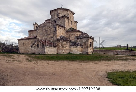 Church of the Annunciation urue�±a located in Spain, is decorated with Lombard Romanesque style, is surrounded by fields. You can see a wall castle in the background