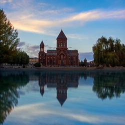Church of the Holy Saviour (being reconstructed after the 1988 earthquake. Gyumri, Armenia) is reflected in the pond at the beautiful sunset