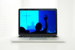 Church services online concept, Home church during quarantine coronavirus Covid-19, Online church from home new normal concept, Cross with worship hand in screen laptop, spirituality and religion.