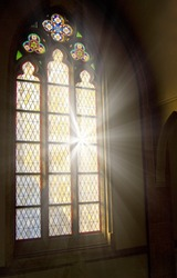 Church stained-glass window with sunlight shining through