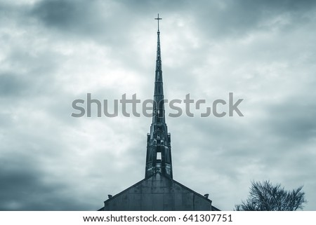 Church steel brass spire. Church building roof with spire and holy cross. Cloudy moody sky background. Minimal architecture design and detail. Exterior design and detail. Abstract architecture.