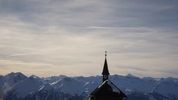 Church steeple and bell tower silhouetted against jagged mountain range and bright cloudy sky, Austrian Alps