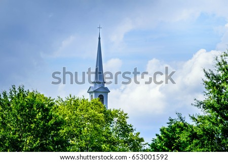 Church steeple in the clouds towering over lush green trees #653001592