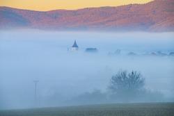 Church tower in autumn morning mist, orange light in background