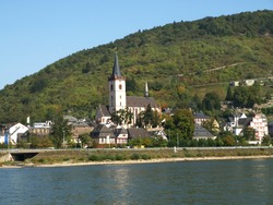 Church with a large bell tower at the front and a smaller one at the back on the bank of the river Rhine