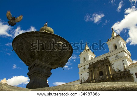 Church with pigeon flying on fountain and blue skies, shot at historical center of Quito, the capital of Ecuador