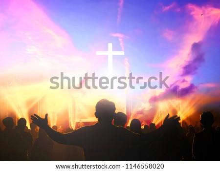 Church worship concept:Silhouette of Christian prayers raising hand while praying to the Jesus