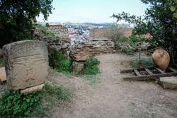 Church yard, tombstone, stone, jug, stairs. ruined stone wall. Religion. Summer, green plants, bushes. Georgia, Tbilisi, Narikala fortress.
