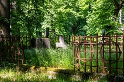 Churchyard old burial ground and fence in graveyard surrounded with green trees. Vintage grave with rusty metal railing and broken stone cross at European cemetery