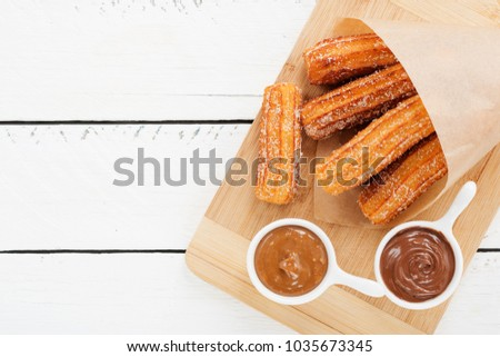 Churros with sugar and chocolate sauce . top view  #1035673345