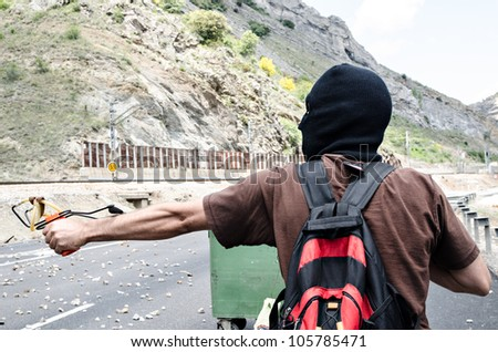 CIÑERA, SPAIN - JUNE 19: Striking miners test a slingshot at the National 630 Highway to keep police vehicles from driving into town on June 19th 2012 in Ciñera, Spain.
