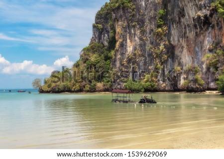 CiÄ…gnik   z przyczepÄ… przystosowanÄ… do transportu turystów z Å'odzi na lÄ…d w pobliżu Railay Beach na Krabi w Tajlandji. Zdjęcia stock ©
