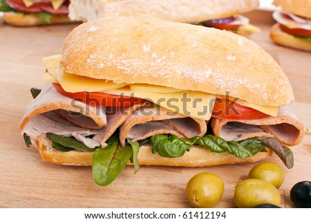 Ciabatta bread sandwich stuffed with meat, cheese and vegetables