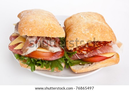 Ciabatta bread sandwiches stuffed with meat, cheese and vegetables on white background - stock photo