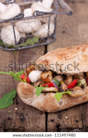 Ciabatta bread with fresh mushrooms, cheese and vegetables on wooden table, fresh mushrooms in a basket