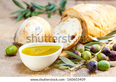 Ciabatta bread with olive oil and olive branch on burlap.