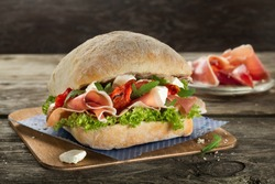Ciabatta burger sandwich with proscuitto ham, mozzarella and salad close up on the wooden background