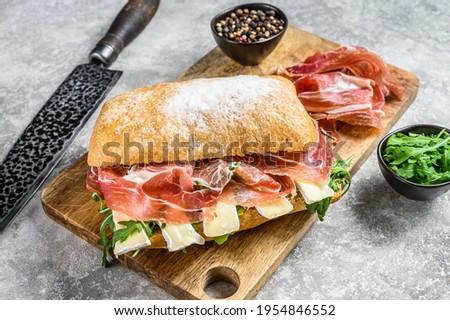 Ciabatta sandwich with prosciutto crudo ham, arugula and camembert brie cheese. Gray background. Top view Stock photo ©
