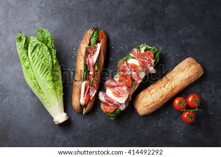 Ciabatta sandwich with romaine salad, prosciutto and mozzarella cheese over stone background. Sandwich ingredients. Top view